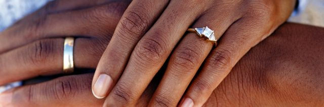 Hands of married couple wearing wedding rings.
