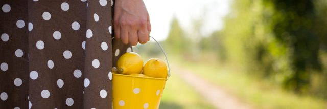 A close-up of a woman holding a yellow bucket of lemons.