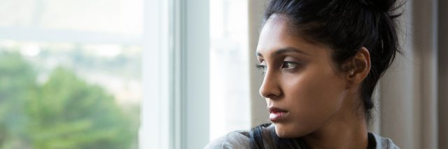 A young woman looking out her window, looking as though she's reflecting.