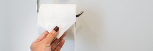 A close-up of a woman pulling on toilet paper.
