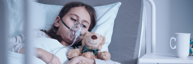 A picture of a child laying in a hospital bed, wearing an oxygen mask.