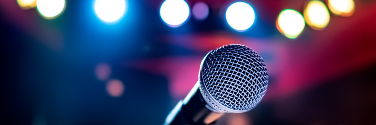 Microphone on stage against a background of auditorium.
