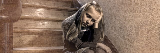 Depressed and worried schoolgirl sitting on staircase.