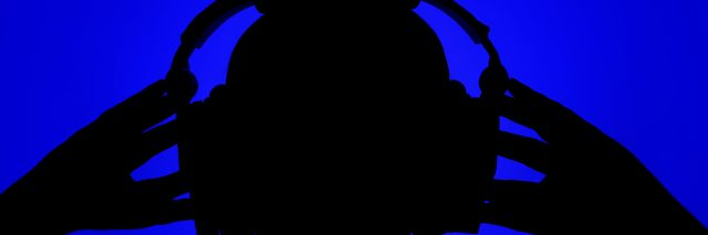 Silhouette of man with headphones on blue background.