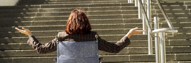 Woman in a wheelchair at the bottom of a flight of stairs.