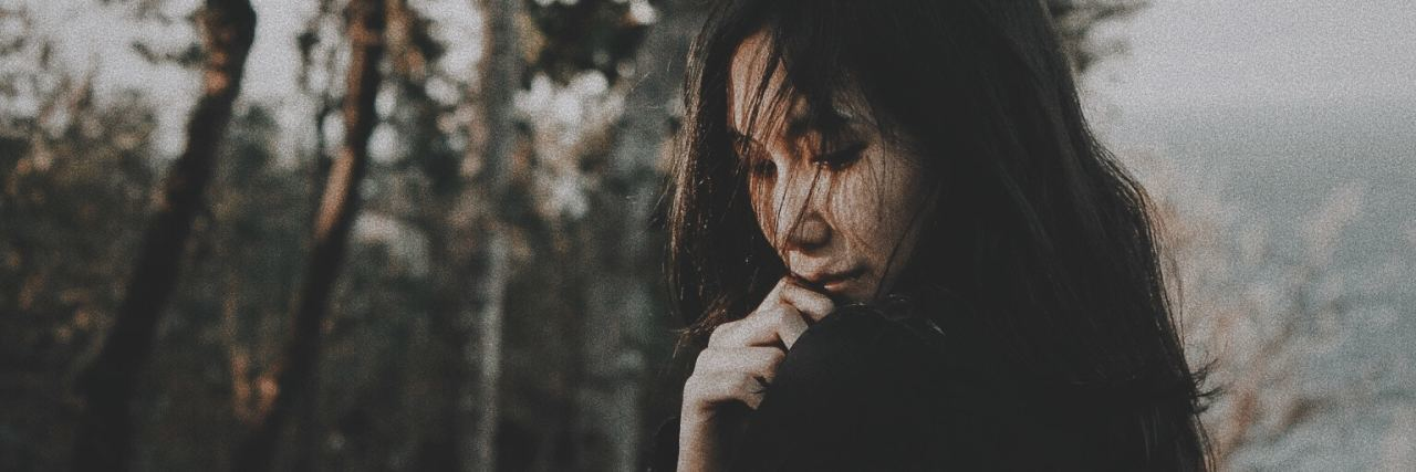 young asian woman looking depressed in front of trees