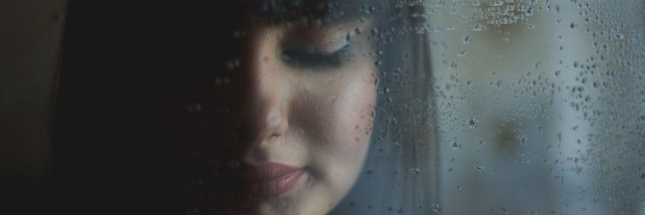 woman against rainy window at night closed eyes