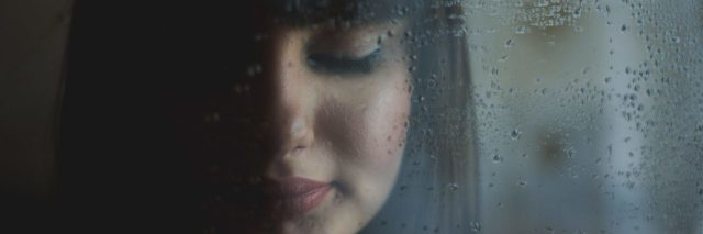 woman against rainy window at night closed eyes
