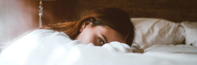 woman leaning on bed looking at camera tired