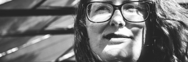 stock black and white photo of woman with glasses squinting in sunlight
