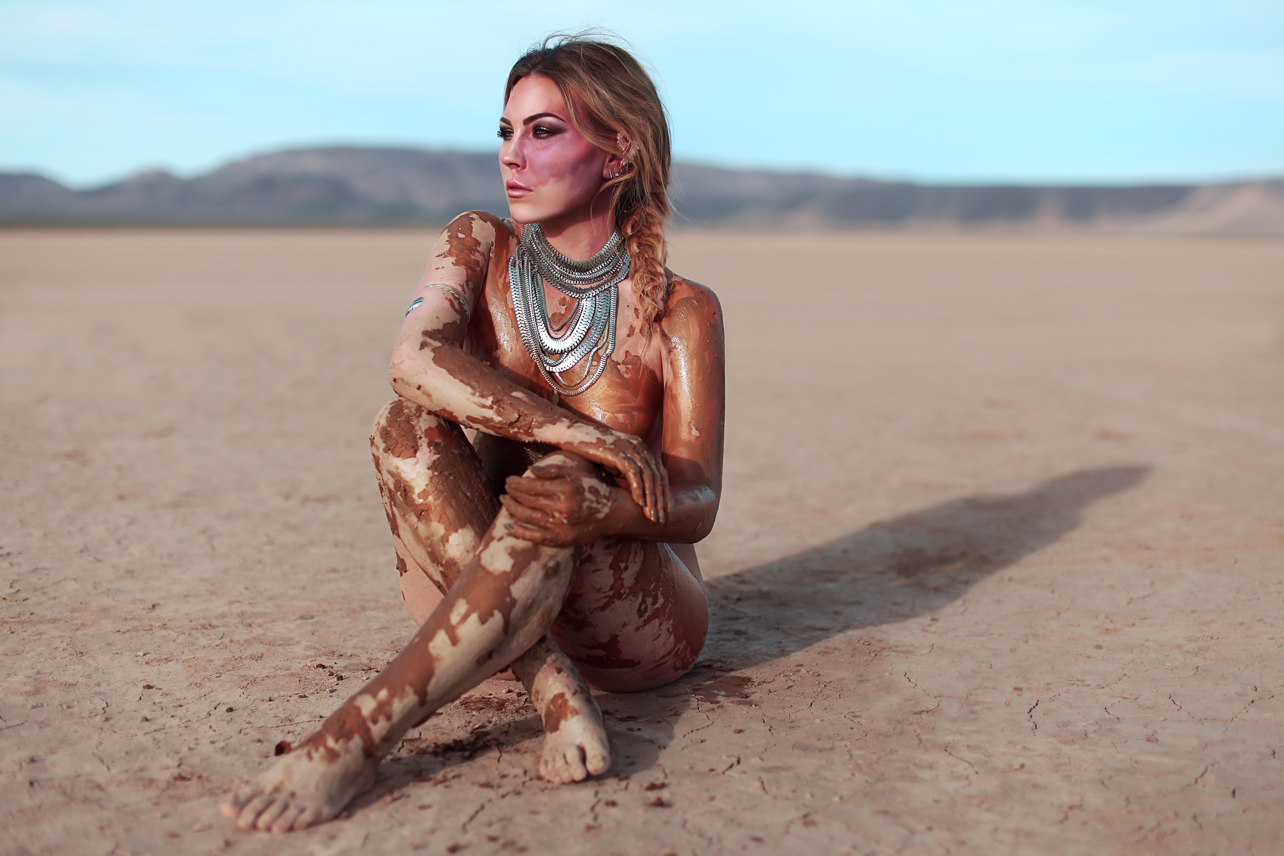 Paige sitting on some sad, covered in mud, looking away from the camera s her birthmark stands out on her face and neck.