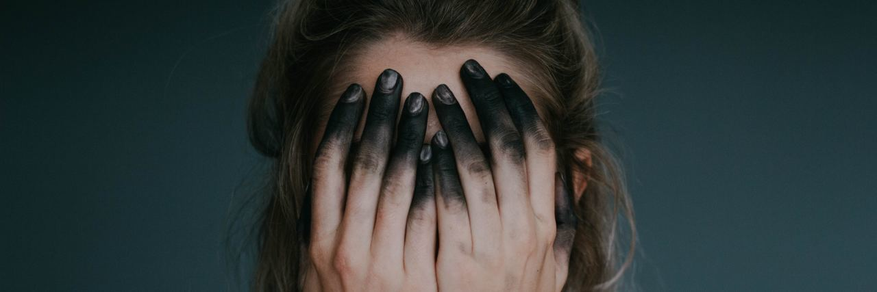 woman covering face with hands stained with black ink