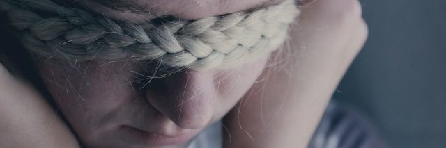 young blonde woman covering eyes with hair braid