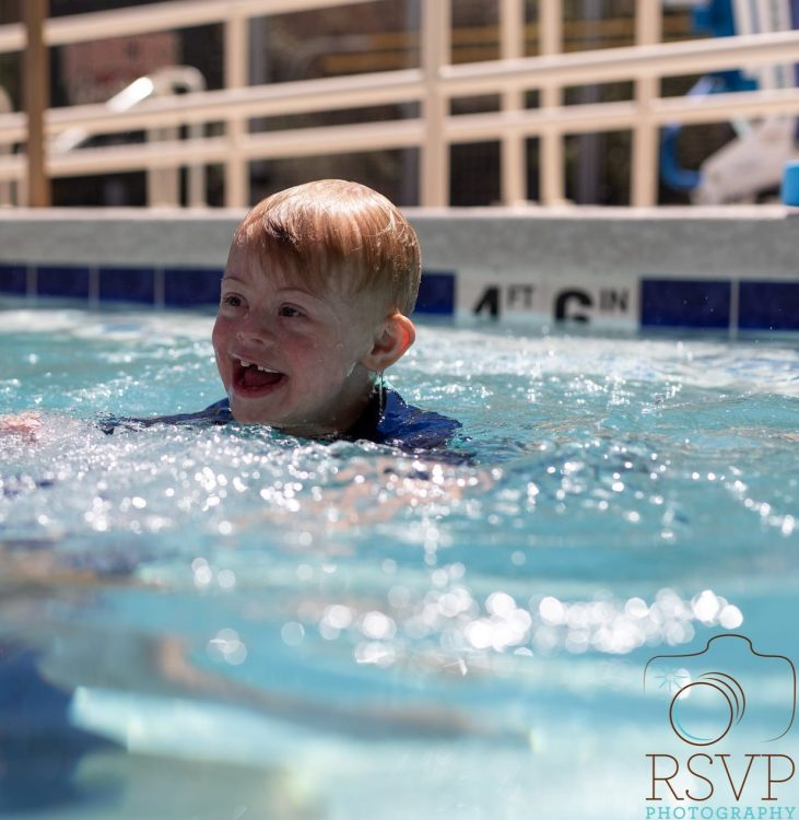 Boy with Down syndrome smiling in pool