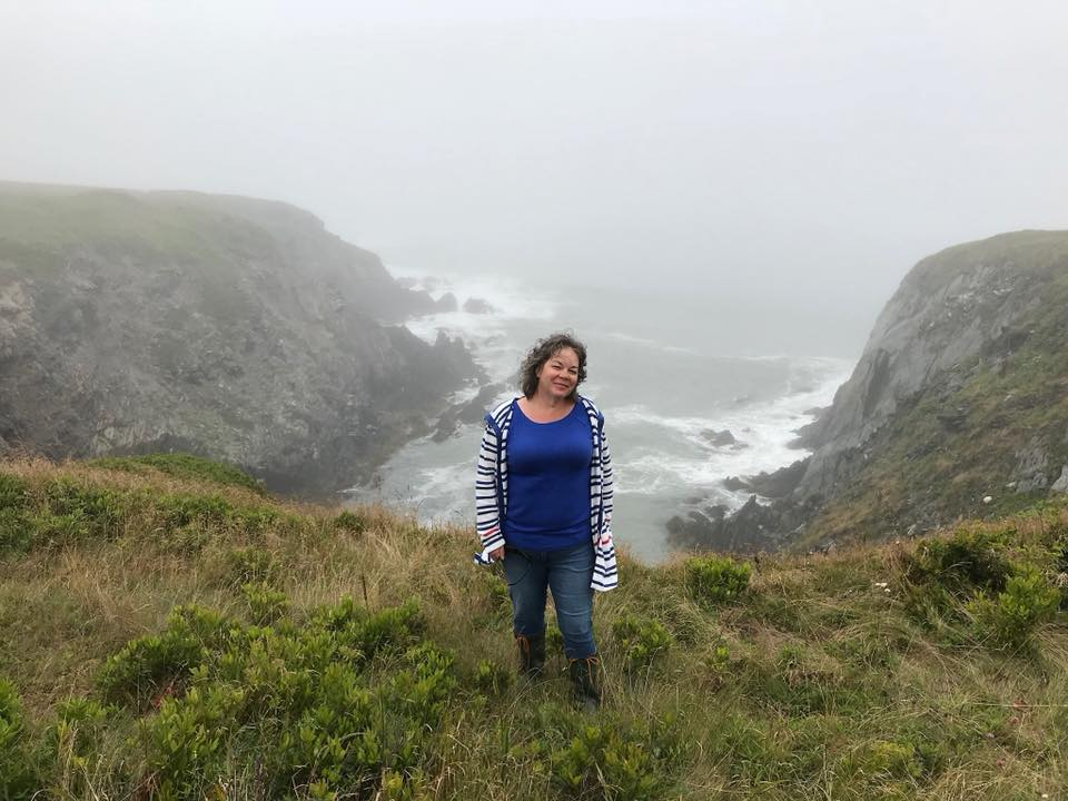 woman standing on a cliff in nova scotia