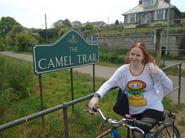 woman posing on her bike in front of a sign that says 'the camel trail'