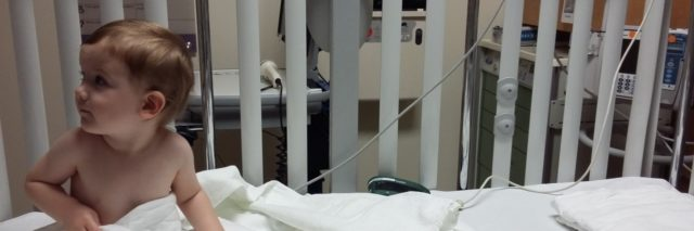Boy in hospital bed sitting up looking to the side