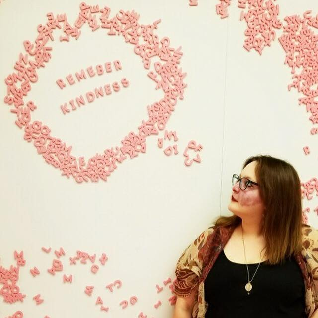 "A picture of the writer standing in front of a magnetic wall covered with pink magnetic letters. Above Crystal, she created a speech bubble out of letters, and as she looks at it, it reads, ""Remember kindness."""