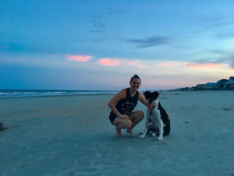 woman and her dog on the beach at dusk