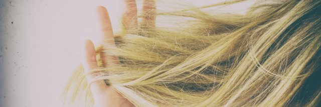 Woman's hand running her fingers through tangled hair.