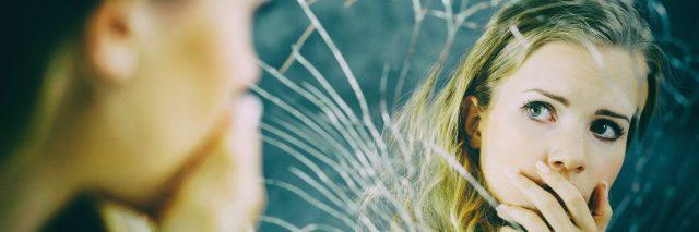 Girl looking in broken mirror.