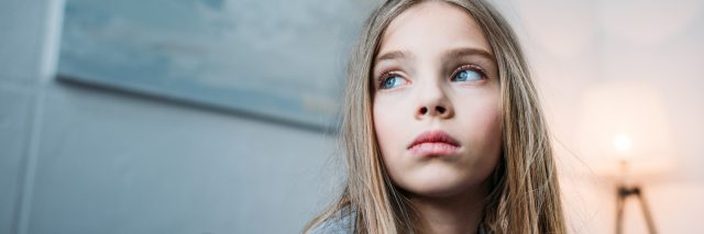 A picture of a young girl wearing a serious facial expression, looking away from the camera.