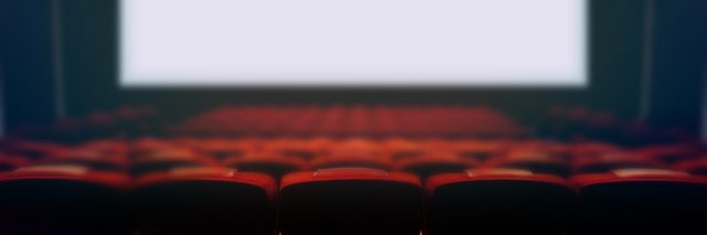 Empty movie cinema seats with blank wide white screen.