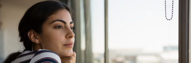 Thoughtful young beautiful woman looking through window at office