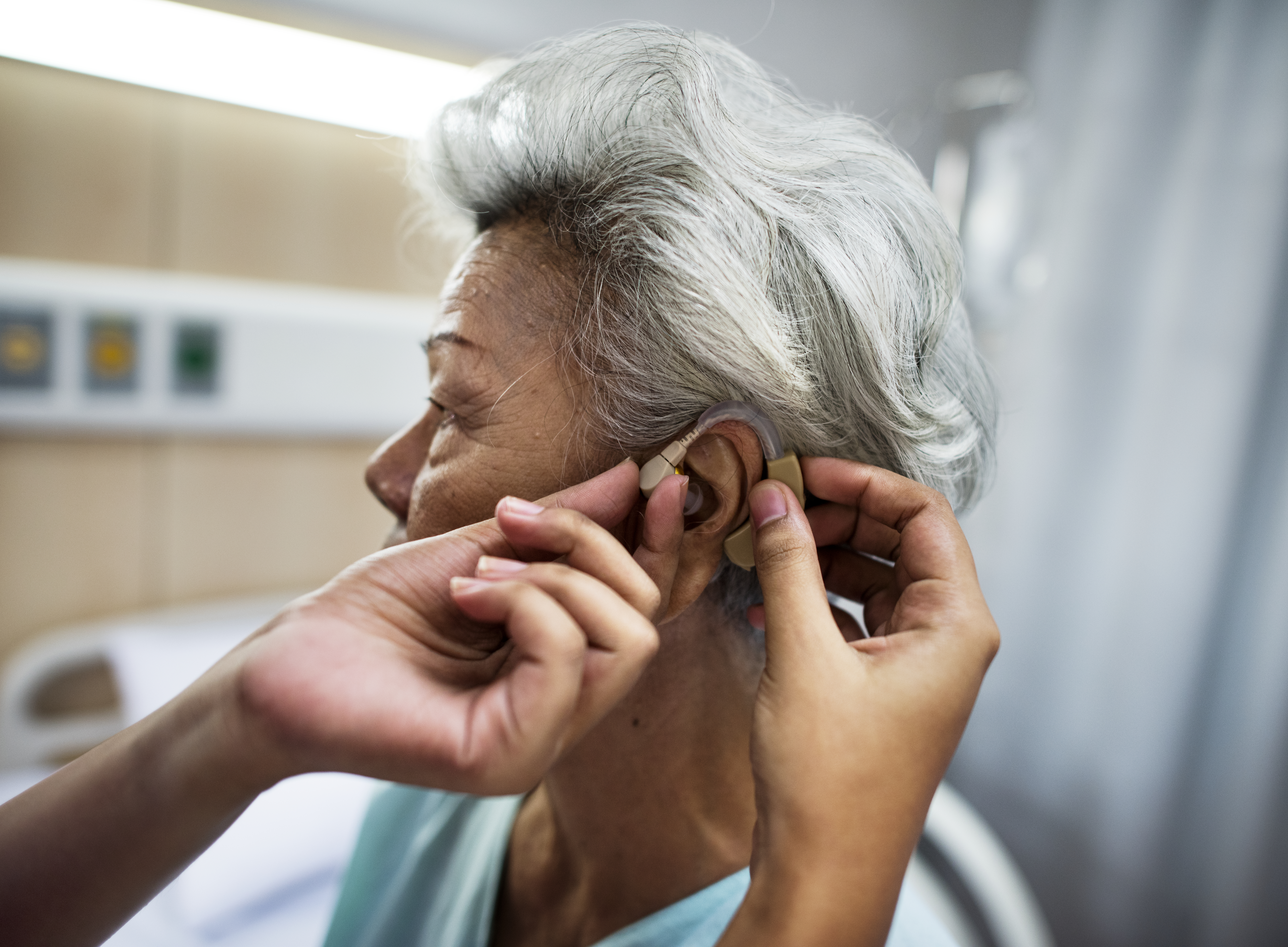 Elderly woman being fitted for a hearing aid.
