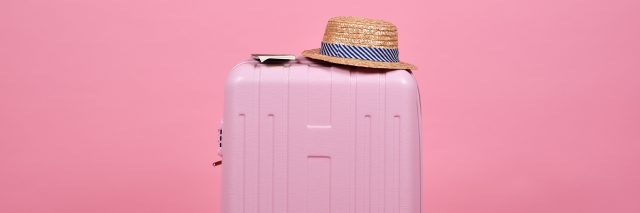 A light pink suitcase with a sun hat in front of a darker pink suitcase.