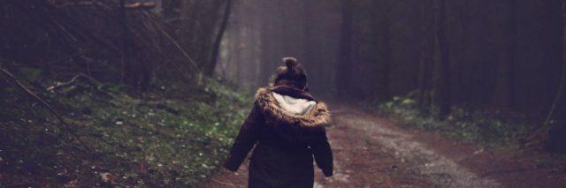 little girl walking alone through forest
