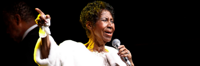 Aretha Franklin performing with a white coat on