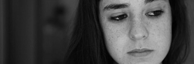 black and white photo of young woman with freckles looking sad
