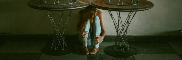woman hugging knees under tables against wall