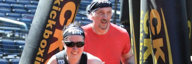 Jess with her sighted guide in a Spartan race. She is running ahead of him.