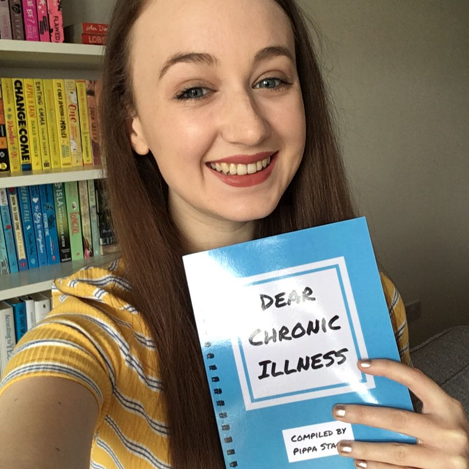 Pippa smiling and holding a copy of 'dear chronic illness' book