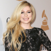 Avril Lavigne on a red carpet wearing a black lacy and long sleeve gown.
