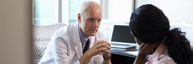 A doctor talking to a patient in his office.