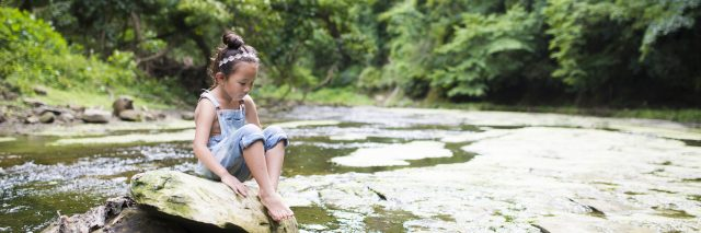 Little girl playing in a stream, daydreaming.