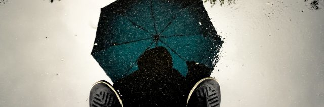 looking up at man holding umbrella from point of view on ground