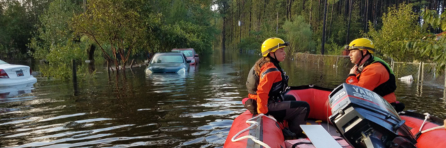 Two rescuers sit in a red raft in flood waters in North Carolina after hurricane Florence.