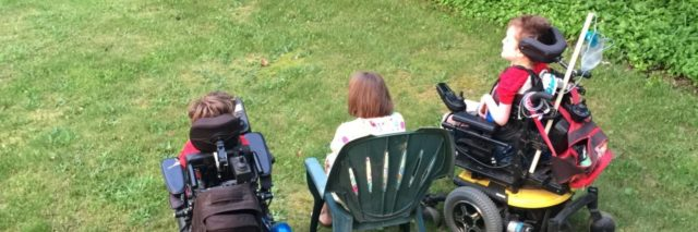 Back of two sons in wheelchairs, mom sitting on a lawn chair in the middle, they are all facing the street watching cars go by