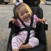 Adorable little girl with Down syndrome sitting on her stroller and smiling at the camera