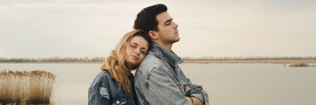 A woman resting her head on a man's shoulder. They're standing in front of water. The sky is grey