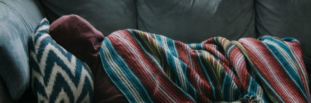 man lying on sofa covered by colorful blanket
