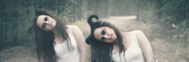 Two twins demons with horns in forest.