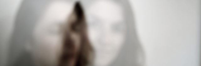 A double-exposed image of a woman standing in front of a white background.