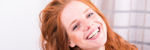 A picture of a red headed woman smiling.