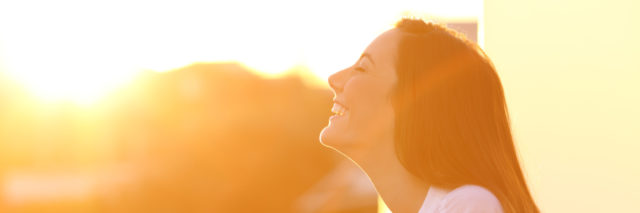 Woman looking towards the sun and smiling.