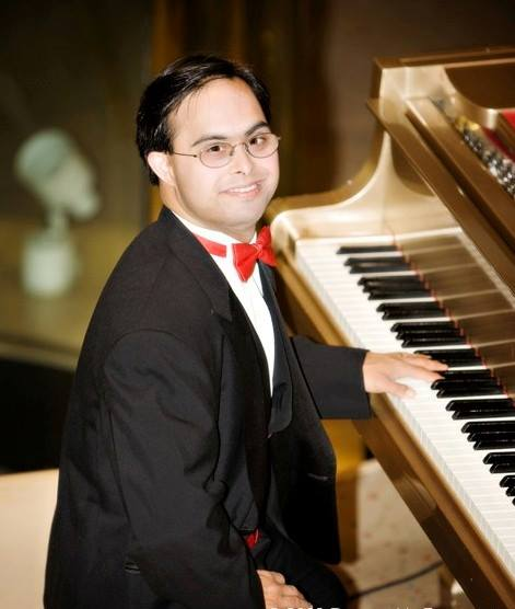 Sujeet Desai wearing a tuxedo and sitting at the piano, smiling at camera